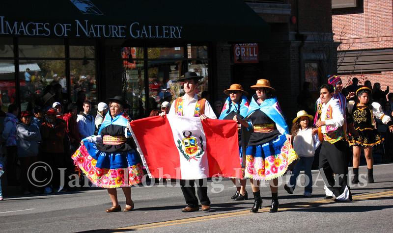 Peruvian families in colorful, traditional costumes carry the flag of their homeland in the Trailing of the Sheep Festival parade, Ketchum, Idaho.