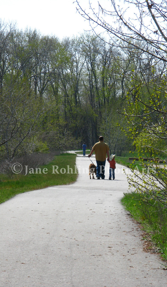 Father and son walk their dog on the greenbelt along the Boise River in Eagle, Idaho.