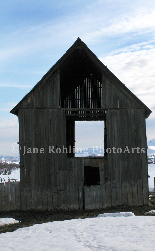 A weathered barn near Ola, Idaho offers a window to the snowy landscape beyond.