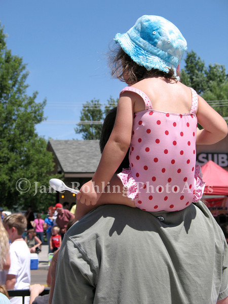 A toddler watches the Eagle Fun Days parade from a great vantage point--her father's shoulders. Eagle, Idaho