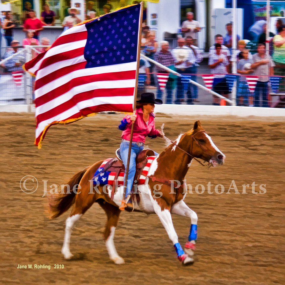 A U.S. flag-bearing cowgirl circles the arena during the 2010 Caldwell Night Rodeo in Caldwell, Canyon County, Idaho.