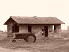 Abandoned Idaho homestead with tractor, sepia