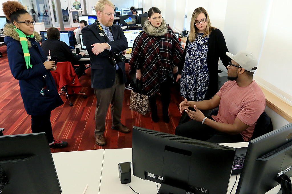 . Fitchburg States University IdeaLab at the Theater Block on Main Street held it\'s ribbon cutting on Tuesday January 29, 2019. After the ribbon cutting FSU senior Denzel Weatherspoon, sitting, from Leominster chatted about his game he designed called Obsolete Souls while in the Game Studio Capstone Course at the IdeaLab with a few of the people that came to the ribbon cutting. SENTINEL & ENTERPRISE/JOHN LOVE