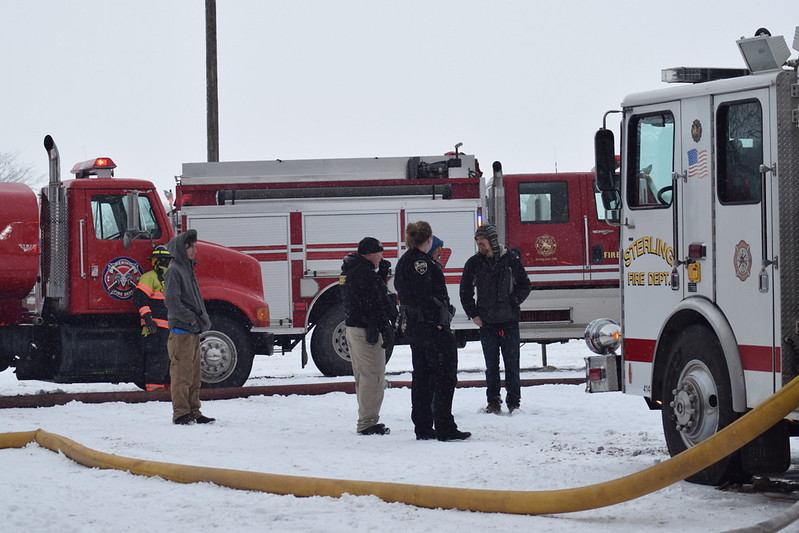 Emergency responders and Iliff residents talk on the scene of a house fire in Iliff Thursday morning, Feb. 1, 2018.