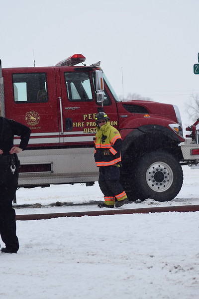 Firefighter next to a Peetz firetruck on scene at an Iliff house fire Thursday morning, Feb. 1, 2018.