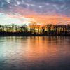 HL 002<br /> <br /> The colors of a winter sunset reflect off the frozen surface of Herrick Lake.  Herrick Lake Forest Preserve, DuPage County, Illinois.