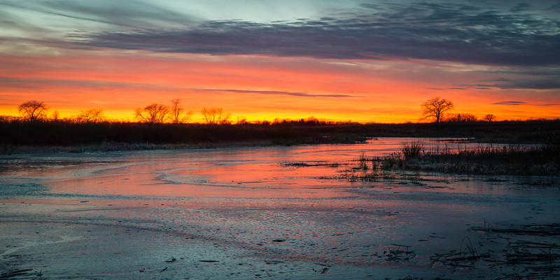 SBP 207<br /> <br /> Bright sunset tones wash across the frozen surface of Crooked Slough at Springbrook Prairie Nature Preserve, DuPage County, Illinois.