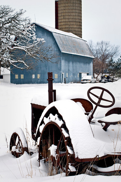 GP 021                   Snow covers the remains of an antique tractor with the Wiedrich Barn in the background at Glacial Park Conservation Area in McHenry County, Ringwood, Illinois.