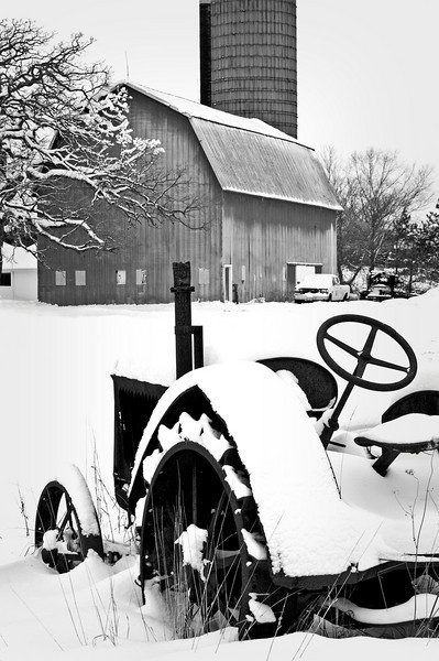 GP 022                     Snow coveres the remains of an antique tractor with the Wiedrich Barn in the background at Glacial Park Conservation Area in McHenry County, Ringwood, Illinois.