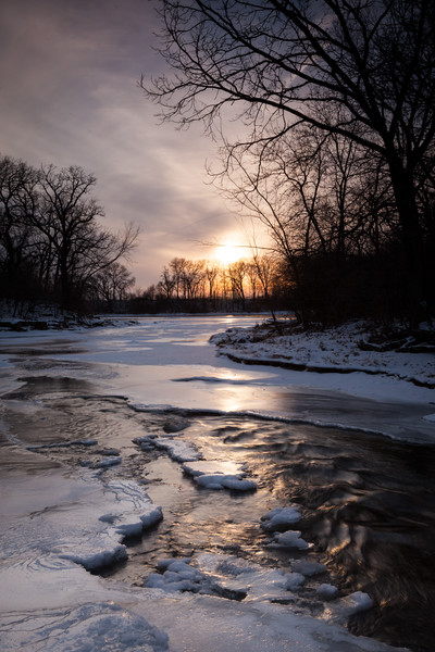 With the approaching sunset, the heavy overscast sky starts breaking up allowing warm light to reflect on the ripples of Prairie Creek. Wilmington, IL<br /> <br /> IL-110121-0027