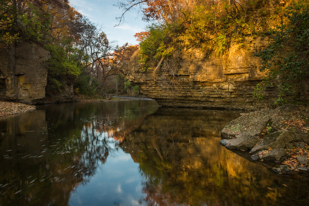 The sunlit bluffs along Rock Creek reflect on the mirror lake surface of water as it winds its way to the Kankakee River. Bourbonnais, IL<br /> <br /> IL-141026-0032