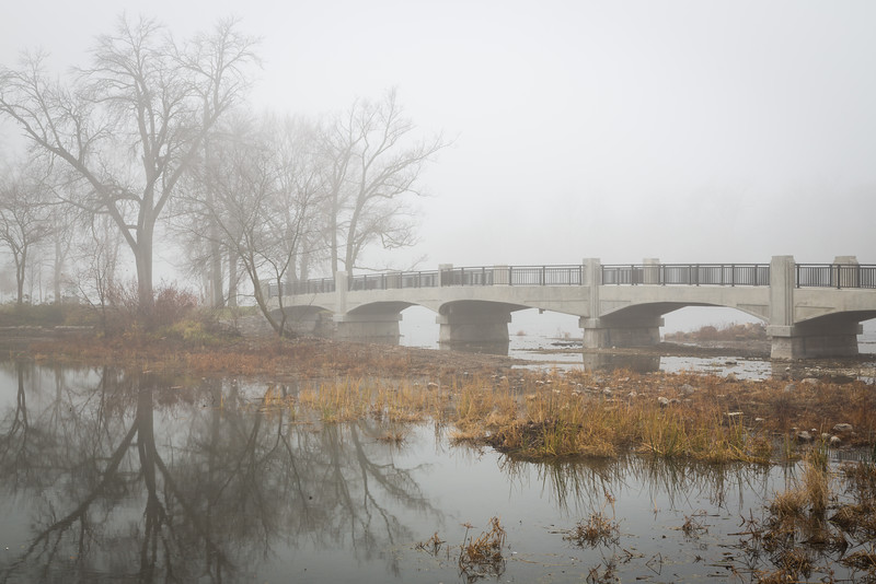 A bridge crossing to one of the many islands of the Fox River. The river level is so low that you can almost walk to the island on the riverbed. Geneva, IL<br /> <br /> IL-121121-0048