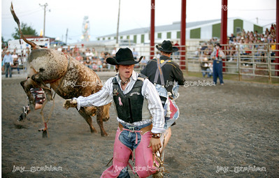 A cowboy runs for safety after falling off a bull during competition at the Coles County fair grounds in Charleston, Illinois on Saturday, August 2, 2008. (Jay Grabiec/Staff Photographer)