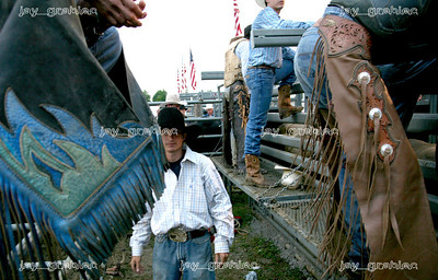 Peewee Helmuth from Arthur, IL, walks behind the shoots during the National Federation of Professional Bullriders competition at the Coles County Fair ground in Charleston, Illinois on Saturday, August 1, 2009.  (Jay Grabiec)