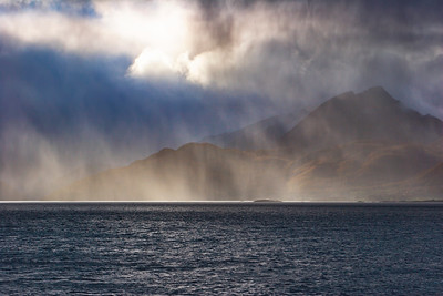 Rays of sunshine illuminate a rain shower