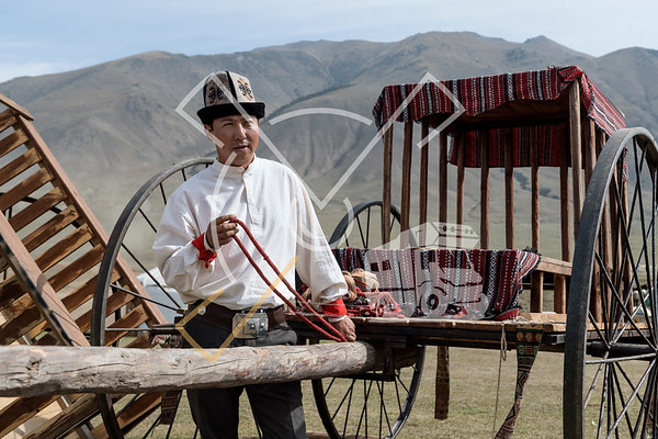 Kyrgyz young man working on carriages and wearing traditional kyrgyz clothes