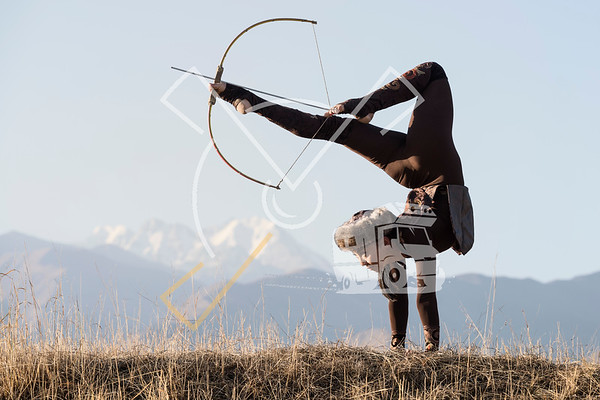 Kyrgyz archer performing foot archery on her traditional costume