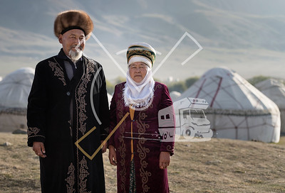 Old couple posing on their traditional Kyrgyz clothes at a yurt camp in Kyrchin, Issyk Kul Region, Kyrgyzstan