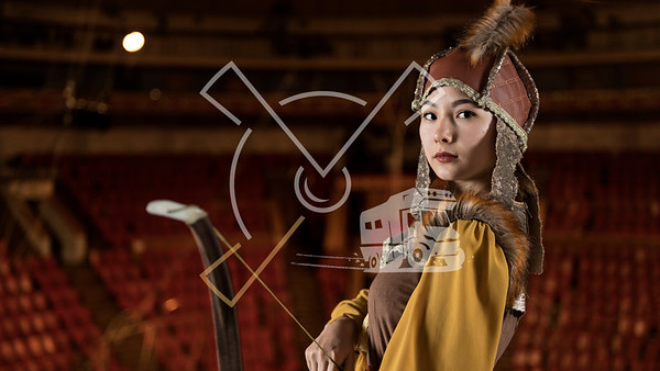Young archer woman from Kyrgyzstan dressed up in traditional archering outfit posing in the Bishkek State Circus building in Bishkek, Kyrgyzstan