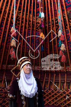 Kyrgyz woman in her colourful yurt wearing the traditional kyrgyz clothes