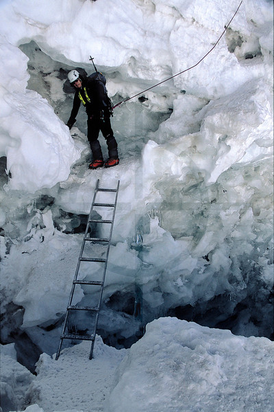 Mountaineer crossing a crevasse by ladder, upper part of Huayna Potosí, Cordillera Real, Bolivia