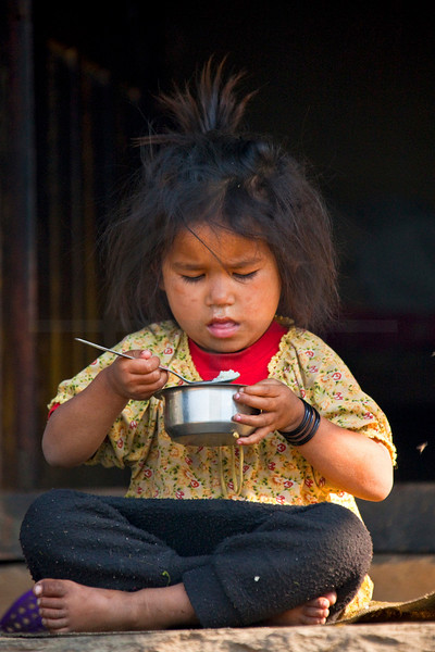 Barefooted girl having breakfast on the terrace in front of her parents' house, Tilche, Annapurna Massif, Nepal