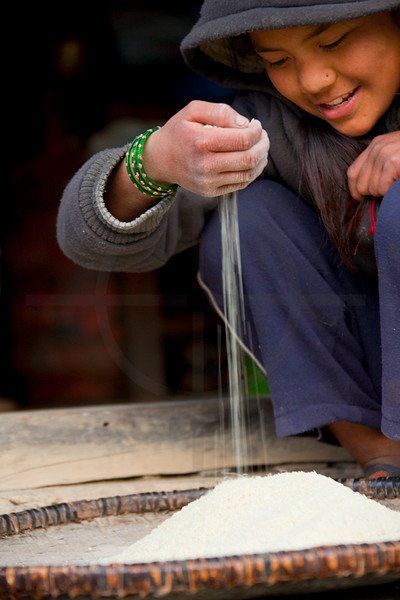 Girl sifitng rice from stones and sticks, Chomrong, Annapurna Region, Nepal