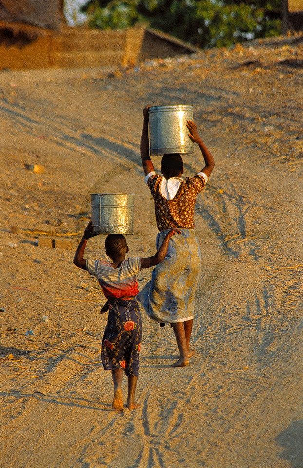 Girls fetching and carrying water in early morning, Monkey Bay, Malawi