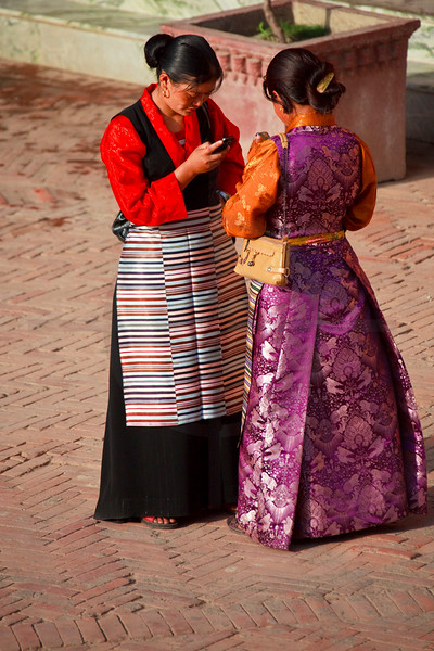 Tibetan refugees in traditional dresses having a modern conversation, Boudhanath, Kathmandu Valley, Nepal
