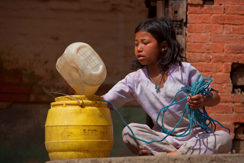 Girl fetching water at a well, Bhaktapur, Kathmandu Valley, Nepal