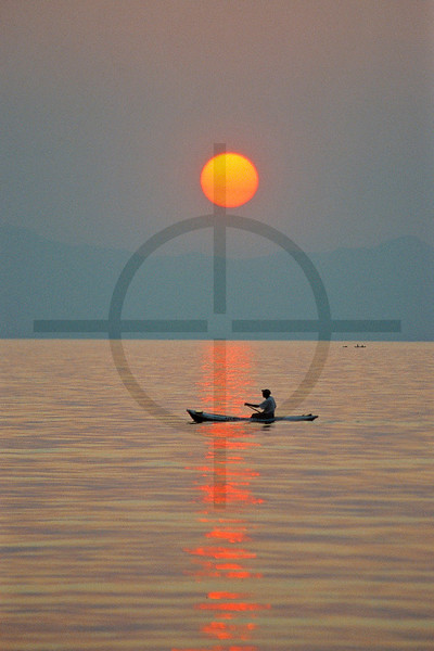 A local paddling at sunset, Lake Malawi, Malawi