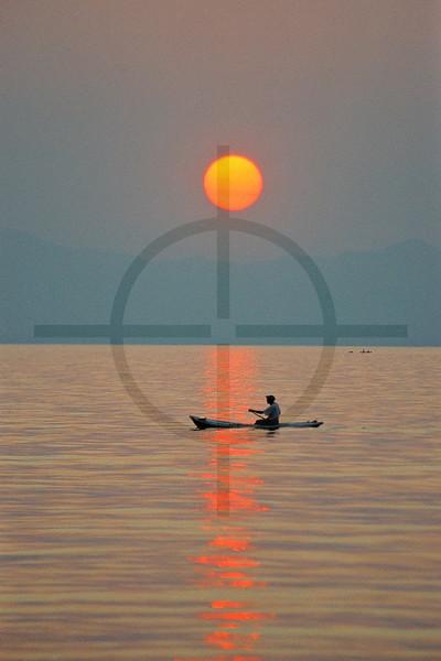 A local paddling at sunset, Lake Malawi, Malawi