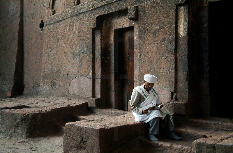 Man reading near a rock-hewn church in Lalibela, Northern Ethiopia