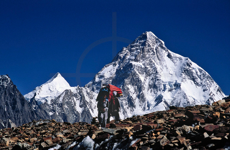 Porters reaching Concordia with Angel Peak and K2 in the background, Karakoram Range, Baltistan, Pakistan