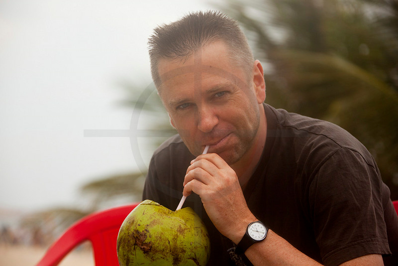 Man drinking fresh coconut juice at Ipanema Beach, Rio de Janeiro, Brazil