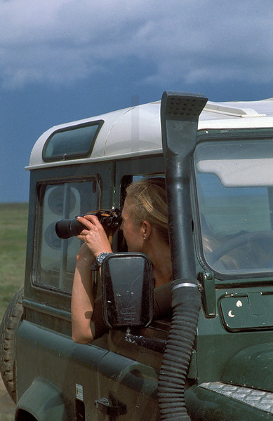 Woman in a landrover with binoculars looking for wildlife, Serengeti National Park, Tanzania