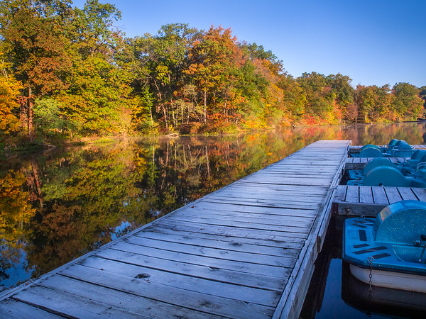 Beautiful Fall colors reflected in the still waters of Lake Shakamak as seen from the floating dock!  Paddle boats sit just waiting for someone to take them on a spin around the lake!
