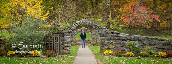 This stone wall and arches surrounding a formal garden at Spring Mill State Park is amazing!  Fall color, a park visitor walking down the path and landscaping added the finishing touches to this scene!