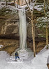 A hiker is dwarfed by the height of this frozen waterfall in Turkey Run State Park one cold Winter day!