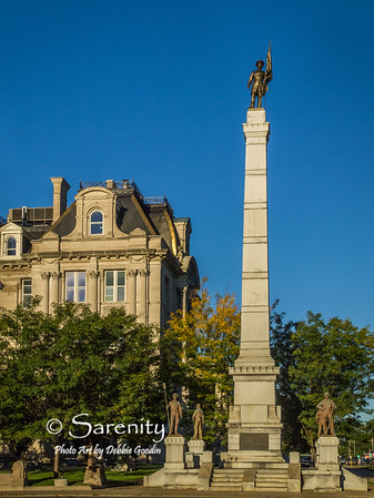 The full length figure of a flag bearer stands atop this tall obelisk at the Soldiers and Sailors Monument on the Courthouse grounds!  To the right at the base is an infantryman holding a rifle.  To the left at the base is an Infantryman holding a ramrod.