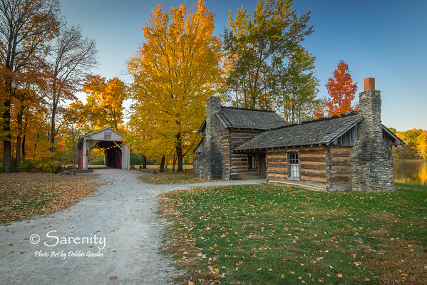 A Fall view of Dog-Trot Cabins and the Irishman's Bridge. These cabins were originally located at Hawthorn Mine near Dugger, Marshall, IL. The bridge was located over Honey Creek on Ferree Road in Riley Township.