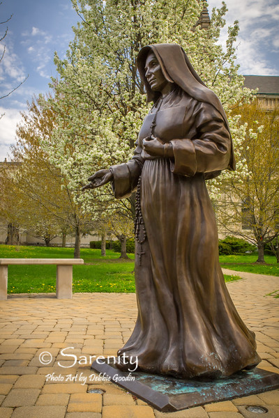 A statue of Saint Mother Theodore Guerin with a backdrop of a tree in bloom on a Spring day! It stands on the campus of St. Mary of the Woods College!