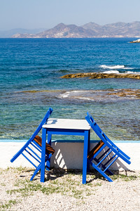 Painted chairs and table by the sea