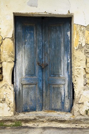 19352249 - old ruin with blue double wooden locked doors as building entrance