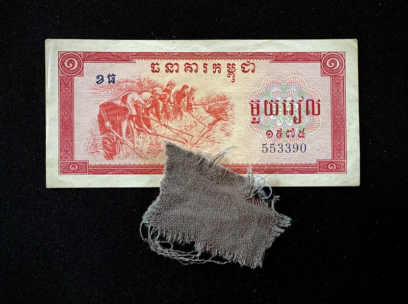 •An unissued Khmer Rouge riel printed in 1975.<br /> <br /> Attempting to create a classless society, the Khmer Rouge abolished money, capitalism, private property, formal education, religion, and traditional cultural practices. Schools, shops, churches, and government buildings were converted into prisons and crop storage facilities. <br /> <br /> •A piece uniform from one of the 8,985 people who were killed at Choeung Ek (the Killing Fields).<br /> <br /> Between 1975 and 1978, approximately 17,000 men, women, children and infants (including nine westerners), were detained and tortured at S-21 prison.<br /> <br /> The remains of 8,985 people, many of whom were bound and blindfolded, were exhumed in 1980 from mass graves in this one-time orchard; 43 of the 129 communal graves here have been left untouched. Fragment of Human bone and bits of cloth are scattered around the disinterred pits.