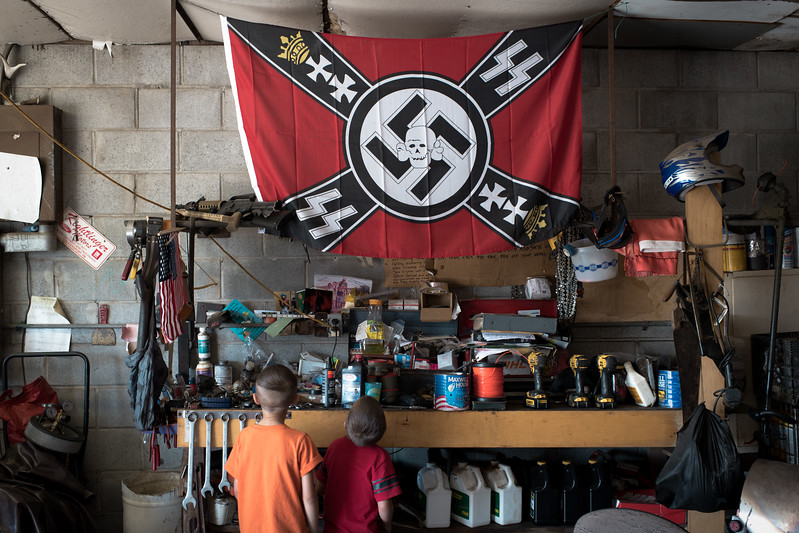 8/25/2018. Brother's Dreysen and Carver, both of who were diagnosed with autism, take a moment to admire their father's new Nazi Waffen SS Banner Skull flag hanging in the workshop. <br /> <br /> In 2013, a year after Dan and Sabrina gave birth to their second child diagnosed with autism, they started reading about National Socialism. The couple felt the diagnosis of both children was somehow related to man-made influences, such as hydraulic fracturing and mandatory vaccinations for children attending public school. After a series of personal and career misfortunes, the ideology of National Socialism fell in line with their core beliefs and quickly became part of their daily lives. <br /> <br /> Today, they remain outspoken members of the White Nationalist movement and have nine children ranging from 4-months to ten years old; four have been diagnosed with autism.