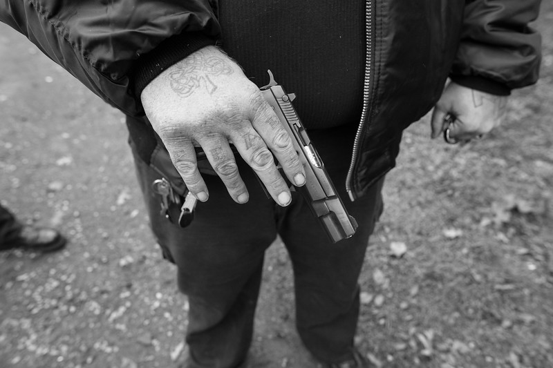 One of the founding members of Aryan Strikeforce shows a glimpse of his pistol and brass knuckles during a state meeting.