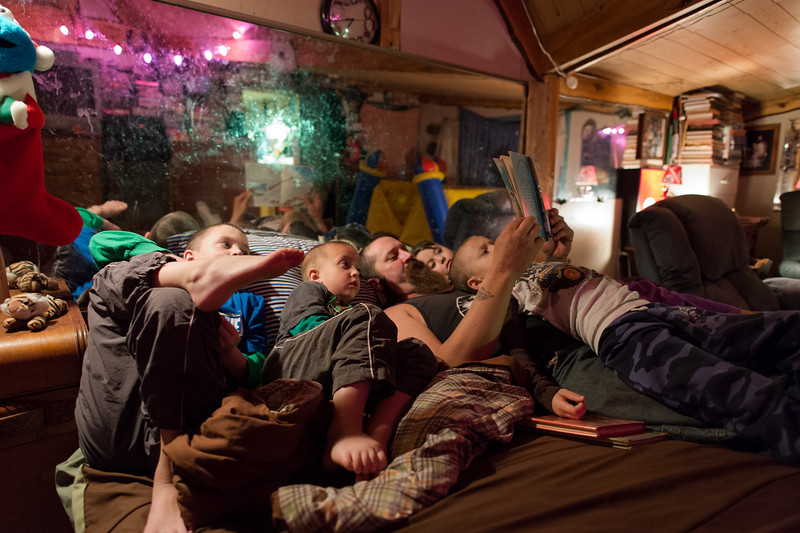 Daniel, a 42-year old wood carver reads a bedtime story to four of his seven children. <br /> <br /> In 2013, a year after Dan and his wife's second child was diagnosed with autism, they started reading about National Socialism. The couple felt the diagnosis of both children was somehow related to man-made influences, such as hydraulic fracturing and childhood immunizations. The ideology of National Socialism fell in line with their core beliefs and quickly became part of their daily lives. <br /> <br /> Today, they remain active members within the White Nationalist movement and have seven children ranging from one to nine, four have been diagnosed with autism.