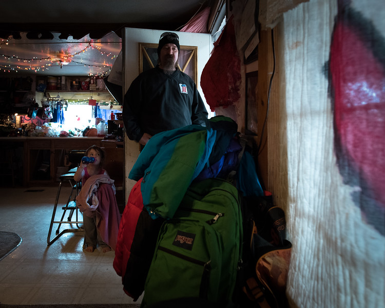 Dan waits for his kids to get ready for the morning bus. In the background a Swastika made up of Christmas lights lines the kitchen ceiling.
