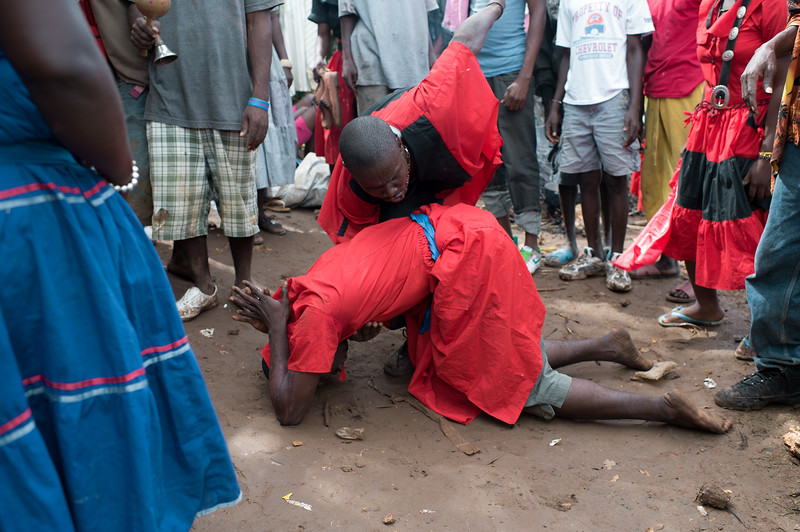 A member of a Vodou Sosyete is overcome by an Iwa (spiritual entity) as a the Hougan (Vodou Priest) helps guide him through the trance like state. <br /> <br /> Each year Vodouisants from all over Haiti make the long pilgrimage to the Grotto of St. Francis de Assisi in the Artibonite mountain region of Haiti. During the fete worshipers may make sacrifices to honor the Iwa and also in gratitude for favors granted or as a payment to a promise made the year prior. Hundreds of animals are sacrificed in and around the grotto, which was once inhabited by Taino Indians.